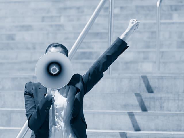Eine Frau, deren Gesicht von einem Megaphon verdeckt ist, reckt die Faus in die Luft.