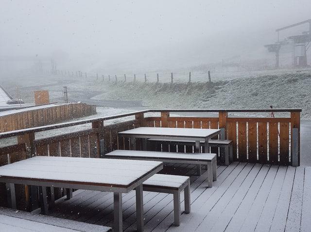 Berghütte mit Bänken und Wiese mit wenig Schnee