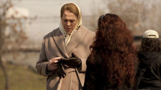 Eine Frau schaut zu Boden. Sie trägt ein Kopftuch und ist gerade dabei, ihre schwarzen Lederhandschuhe auszuziehen. Vor ihr - und mit dem Rücken zum Betrachter - steht eine weitere Frau. Im Hintergrund ist unscharf eine Wiese zu erkennen.