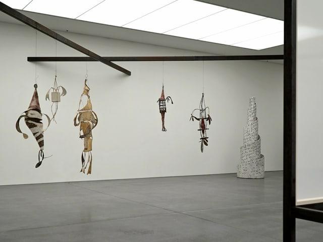 An Stangen hängen Kunstobjekte.