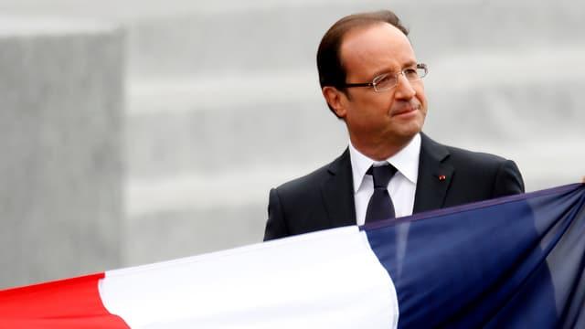 Frankreichs präsident François Holland steht hinter einer französischen Landesflagge. (reuters)