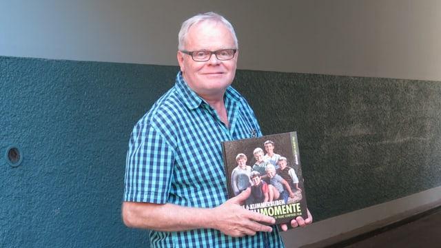 Porträt von Beat Schenk mit seinem Bildband Drehmomente in der Hand
