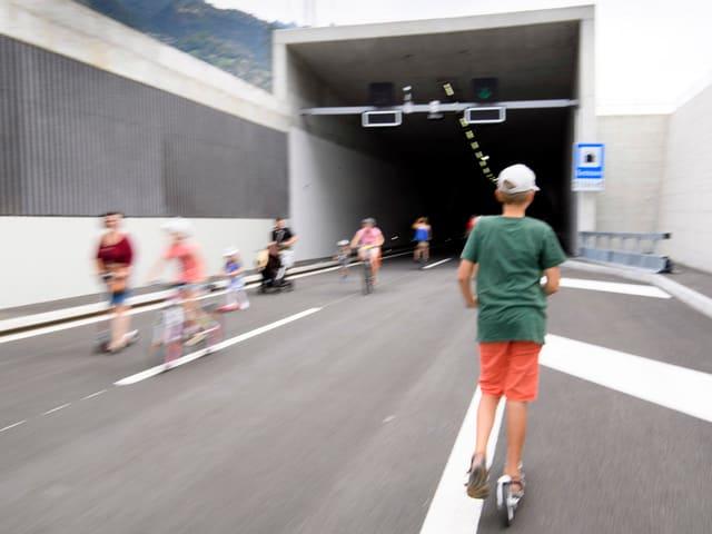 Leute sind auf der autofreien Autobahn unterwegs mit Trottinet und Fahrrad.