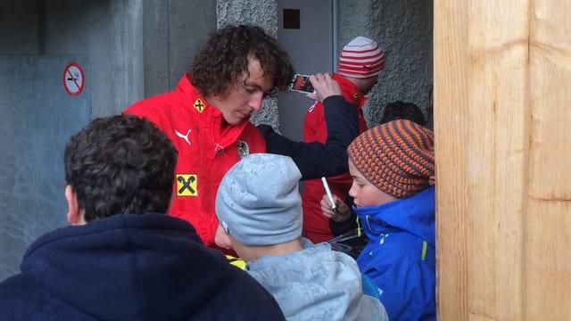Julian Baumgartlinger da la squadra naziunala da l'Austria dat autograms.