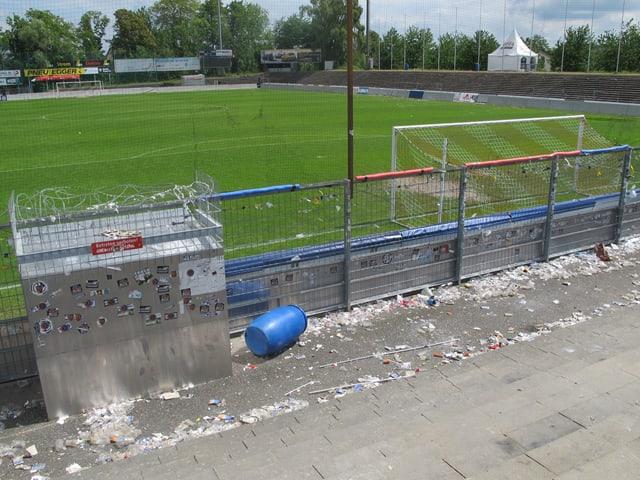 Blick auf das Spielfeld, im Vordergrund Abfall und zerrissene Gitter