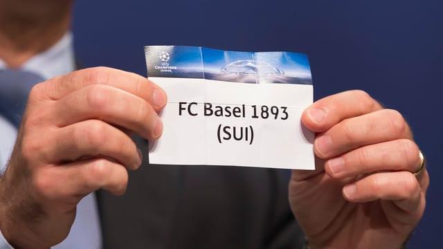 Ein Mann hält einen Zettel hoch, darauf steht Basel.