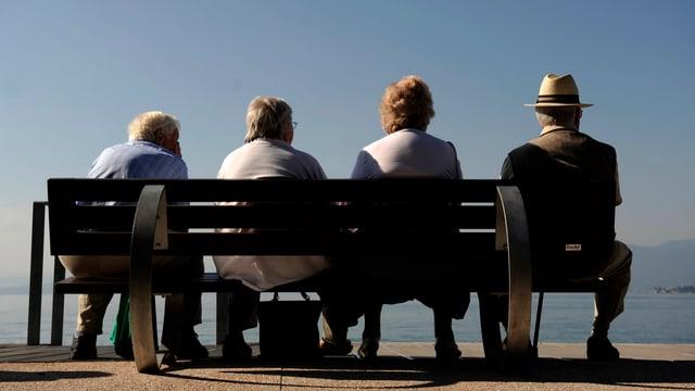 Vier ältere Personen sitzen auf einer Bank mit dem Rücken zur Kamera und blicken auf einen See.