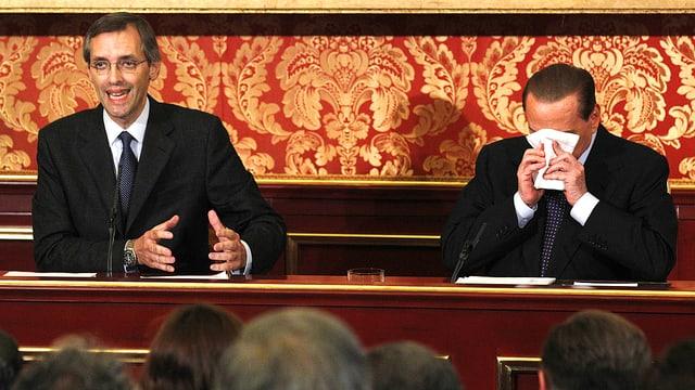 Bild mit Berlusconi und dessen Anwalt Nicoló Ghedini. Berlusconi hält sich ein Taschentuch vors Gesicht.