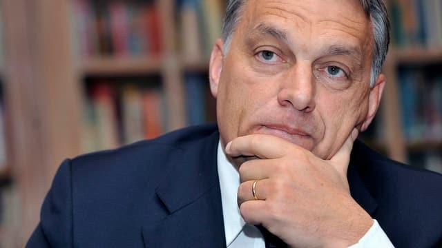 Viktor Orban stützt seinen Kopf nachdenklich auf seine Hand.