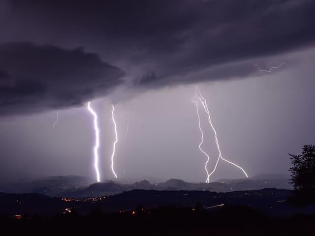 Vier Blitze zucken aus dem grauen Gewitterhimmel.