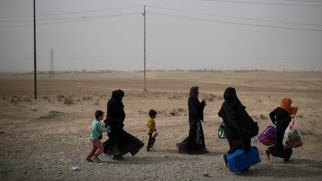Mütter und Kinder flüchten mit Gepäck aus Mossul.