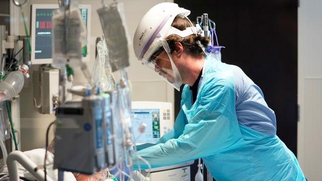 Eine Person mit Schutzausrüstung an einem Krankenbett in einem US-Spital.