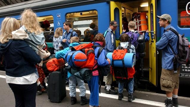 Kinder mit Rucksäcken besteigen einen Zug der SBB.