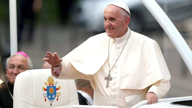 Papst Franziskus winkt aus dem Papamobil der Menge zu.