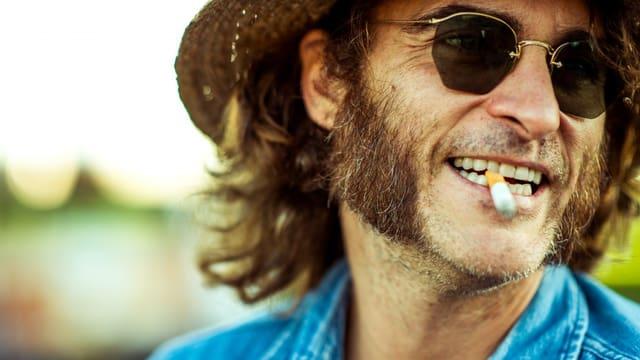 Ein Mann mit Hut, Sonnenbrille, Backenbart und einer Zigarette zwischen den Zähnen.