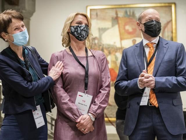 Drei Personen mit Maske
