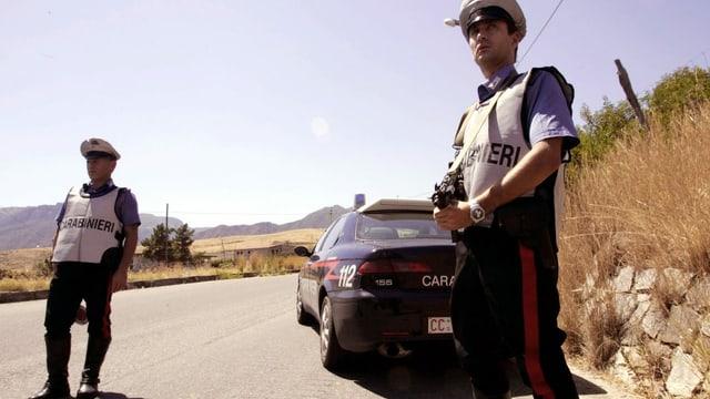 zwei Carabinieri stehen auf einer italienischen Landstrasse und halten Ausschau