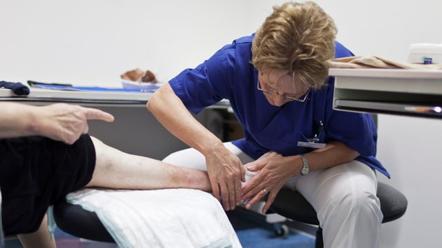 Eine Ärztin behandelt den Fuss eines Patienten