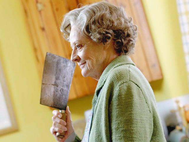 Eine alte Frau mit einem Hackebeil.