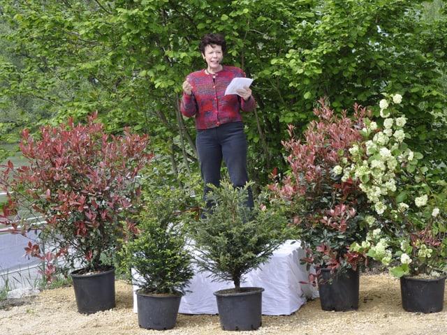 Esther Gassler auf einem Rednerpult vor einem Baum.