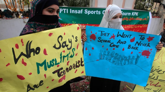 Zwei Musliminnen halten Transparente in den Händen.