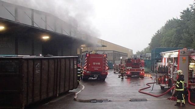 Feuerwehrleute mit mehreren Löschfahrzeugen vor einer Halle.