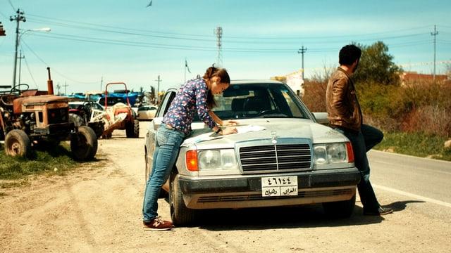 Eine Frau liest die Landkarte auf der Kühlerhaube eines Autos. Ein Mann lehnt sich an das Auto.