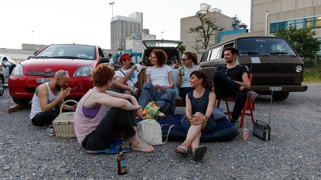 Eine Gruppe sitzt vor Autos.