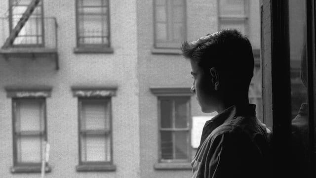 Schwarzweissbild: Ein junger Mann vor einer Hausfassade.