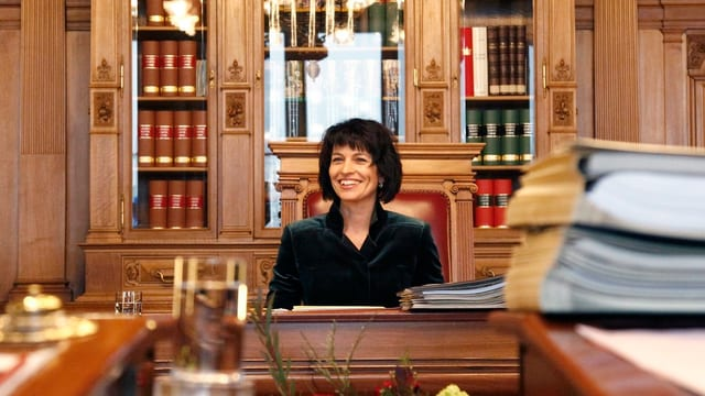 Doris Leuthard, en in biro vegl cun plunas d'actas dasperas.