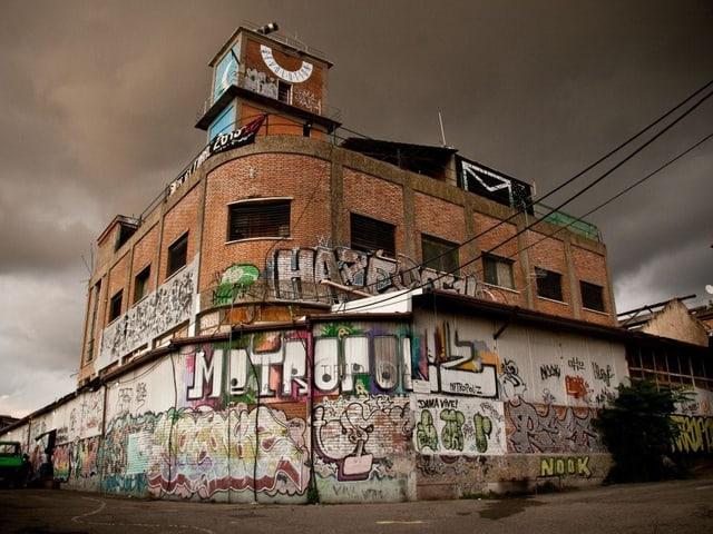 Das MAAM in Rom: Ein mit Graffitis verziertes Backstein-Gebäude, im Hintergrund dunkler Wolkenhimmel.