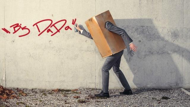 Mann im Karton sprüht an eine Wand.