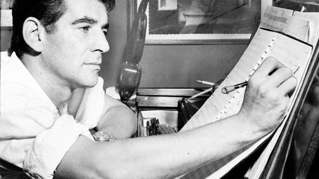 Leonard Bernstein schreibt an seinem Klavier.