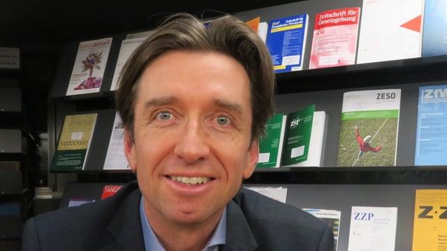 Ein Mann mit braunen Haaren vor einem Büchergestell.