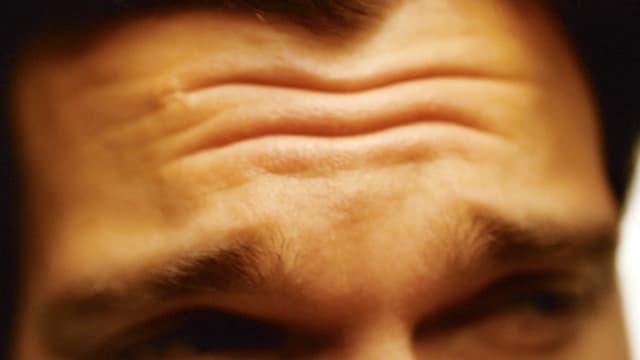 Mann runzelt die Stirn.