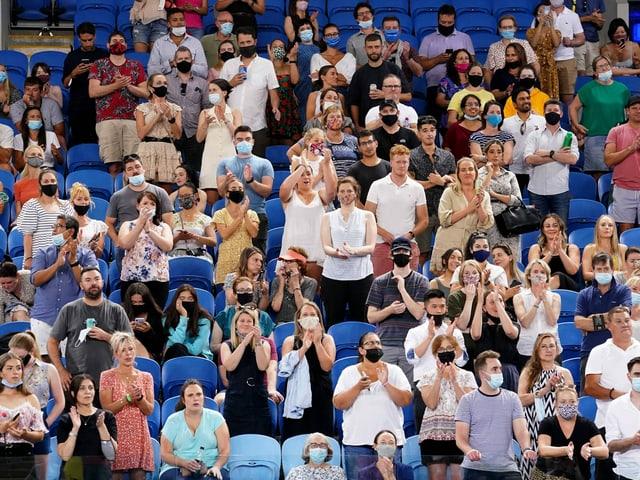 Auf der Tribüne applaudieren Zuschauer den Spielern auf dem Platz.