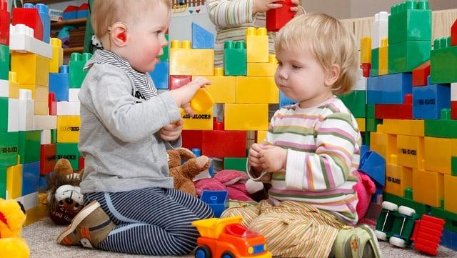Zwei Kinder spielen mit grossen Legosteinen.