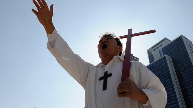 Rufender Mann in weissem Gewand hält ein Kreuz.