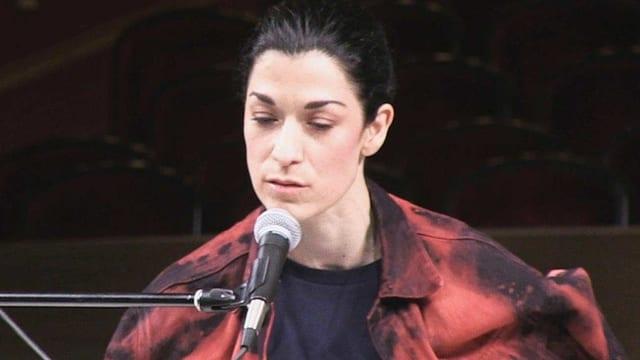 Alexandra Bachzetsis bei einer Performance am Mikrofon.