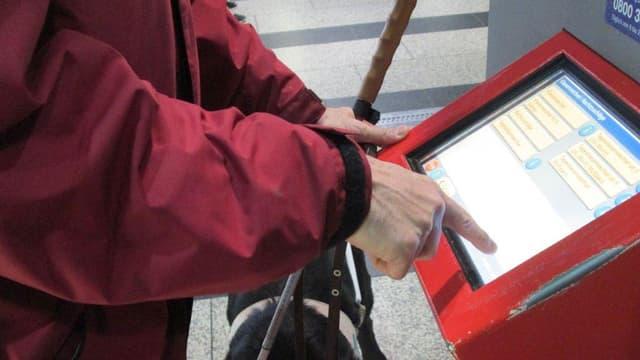 Ein blinder Mann mit Blindenstock in der Hand versucht einen Billettautomaten zu bedienen.