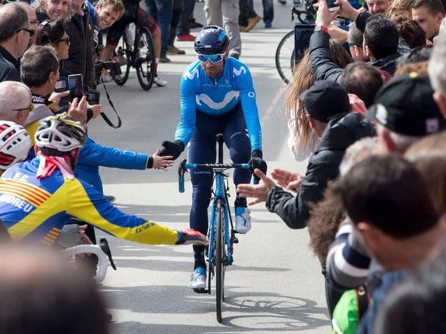 Alejandro Valverde umzingelt von Zuschauern am Strassenrand.