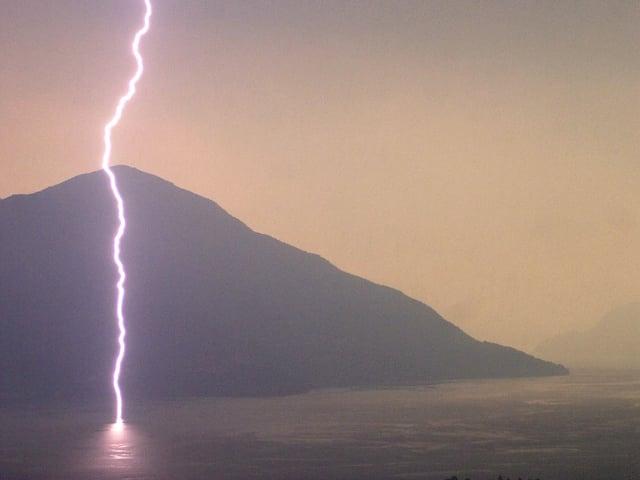 Ein Blitz schlägt vor einer Bergkulisse nachts in ein Gewässer ein.