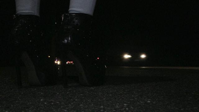 Frau steht in Stöckelschuhen am Strassenrand in Olten, während Autos vorbeifahren.