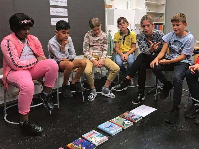 Die Kinder sitzen im Kreis um die ausgelegten Bücher und argumentieren