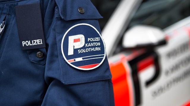 Polizist vor Streifenwagen in Solothurn