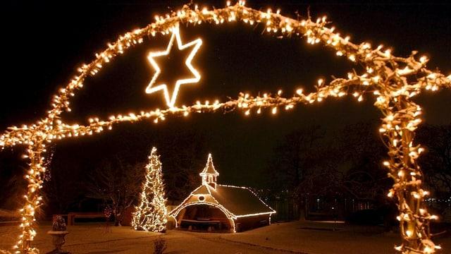Weihnachtlich geschmückter Baum und Haus in einer verschneiten Landschaft.