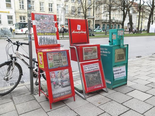 Drei Zeitungsautomaten mit den jeweiligen Titelblättern der Zeitungen.