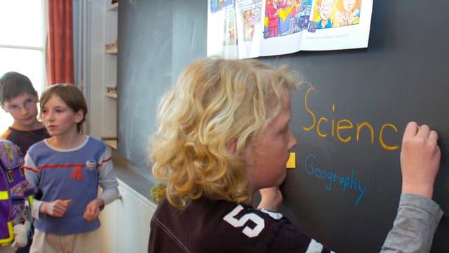 Ein Kind schreibt das Wort «Science» an eine Wandtafel
