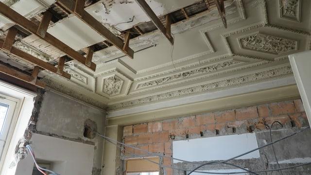 Aufnahme aus dem Innenraum der Villa: Stuckdecke, zum Teil zerstört, offene Wände mit heraushängenden Elektroleitungen