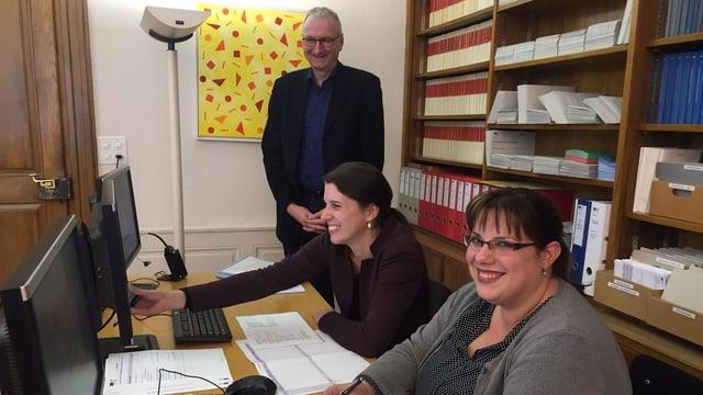 Zwei Frauen sitzen an einem Pult hinter Computern. Ein Mann steht im Hintergrund.